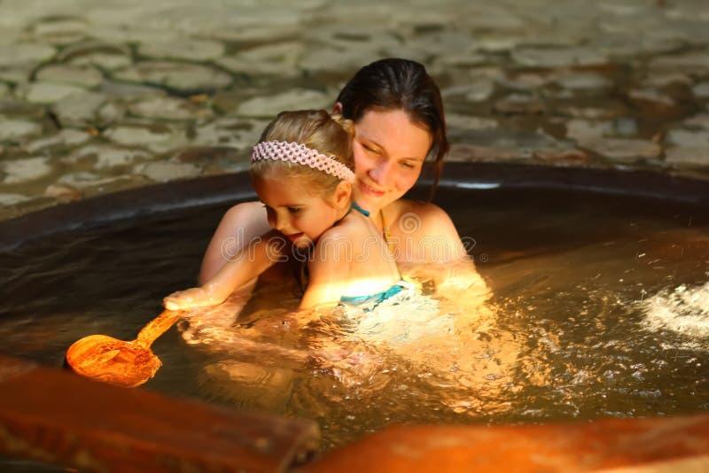 Madre e figlia che prendono il bagno del termale della stazione termale fotografia stock