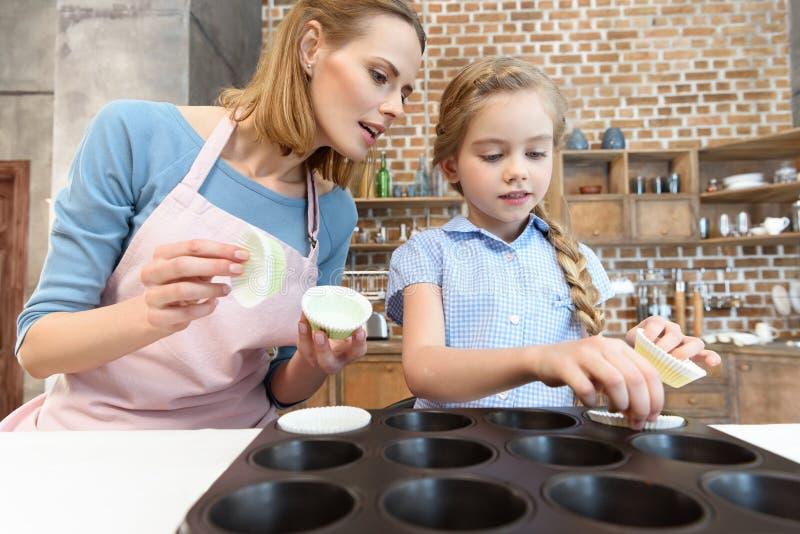 Madre e figlia che preparano forma per cuocere nella cucina fotografia stock