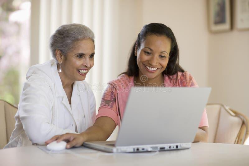 Madre e figlia che ripartono calcolatore fotografia stock