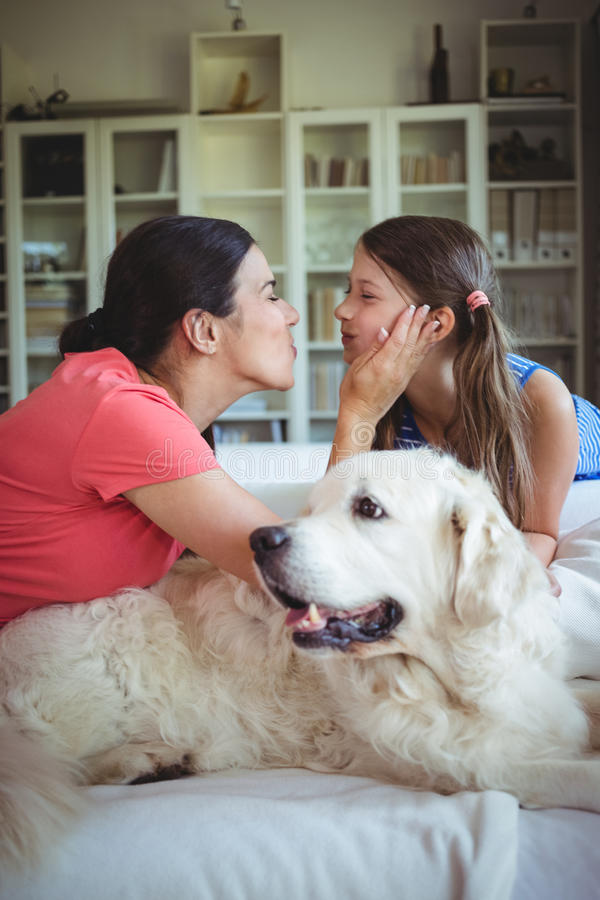 Madre e figlia che si siedono con il cane di animale domestico in salone fotografia stock