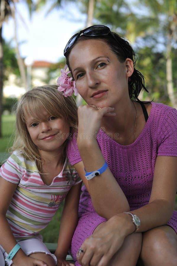Madre e figlia che si siedono insieme fotografie stock