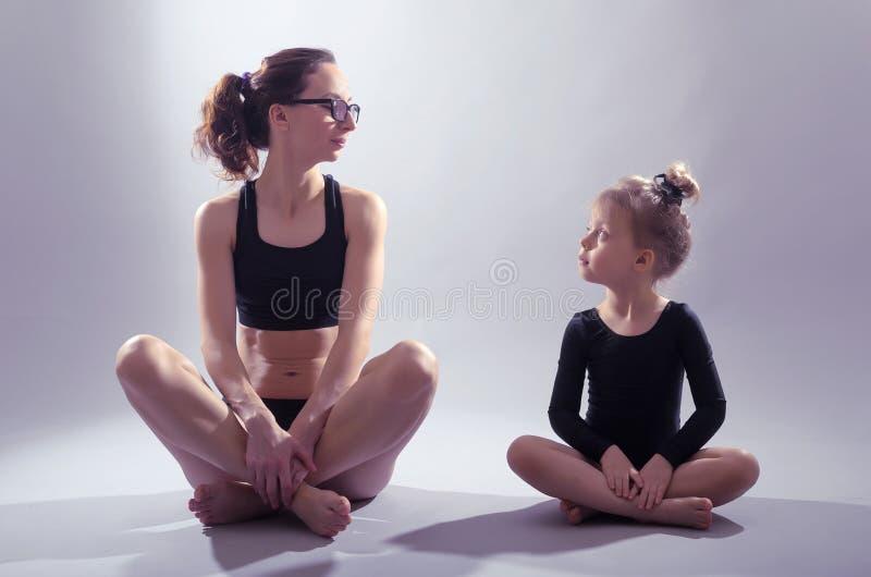 Madre e figlia che si siedono nella posizione di loto su un backgrou grigio immagini stock