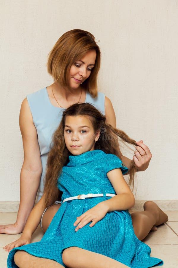 Madre e figlia che si siedono sul pavimento immagini stock libere da diritti