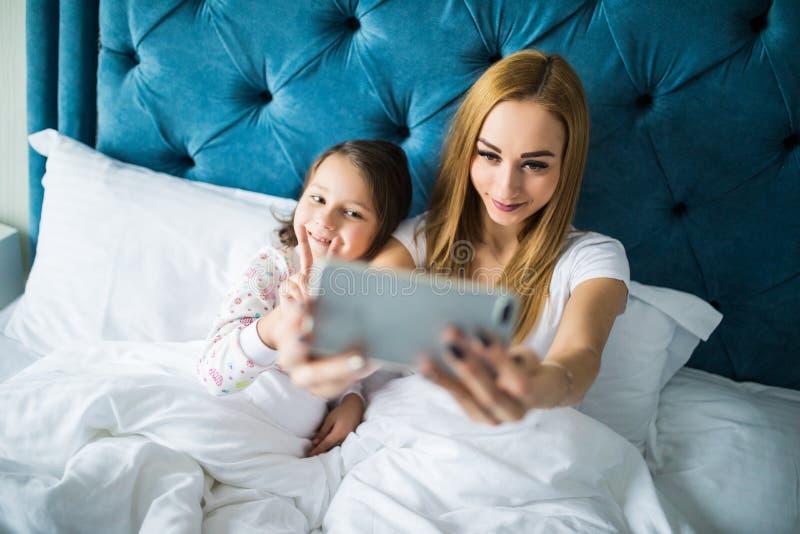Madre e figlia che si trovano sul letto e che prendono autoritratto con lo smartphone Donna che prende selfie con una bambina in  immagini stock libere da diritti