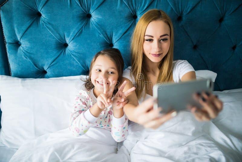 Madre e figlia che si trovano sul letto e che prendono autoritratto con lo smartphone Donna che prende selfie con una bambina in  fotografia stock