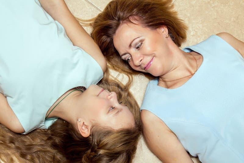 Madre e figlia che si trovano sul pavimento fotografia stock libera da diritti