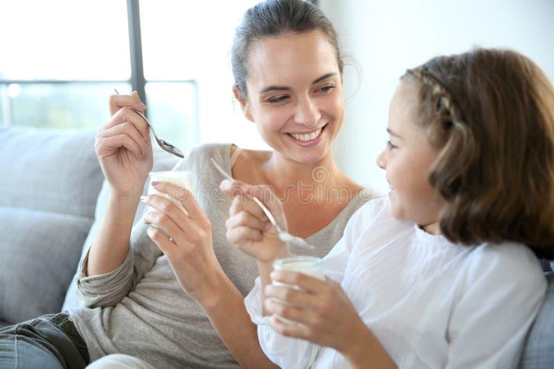 Madre e figlia che sorridono e che mangiano yogurt fotografie stock libere da diritti
