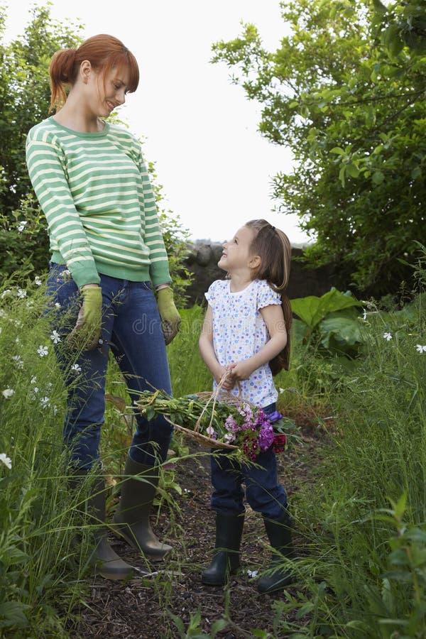 Madre e figlia che stanno nel giardino fotografie stock libere da diritti