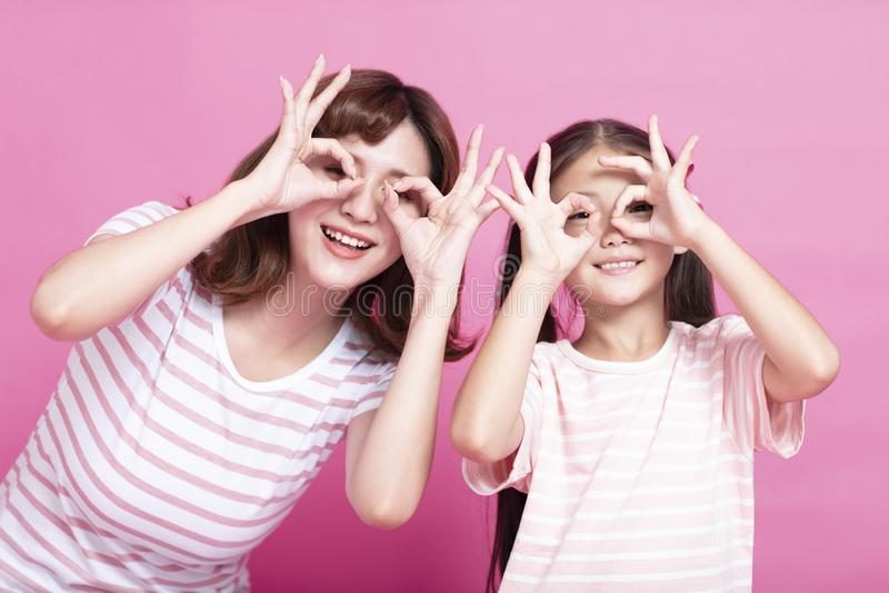 madre e figlia che tengono le dita vicino agli occhi immagine stock