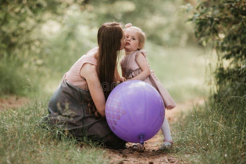 Madre e figlia con i palloni Bella madre felice con la figlia divertendosi nel campo verde che tiene i palloni immagini stock libere da diritti