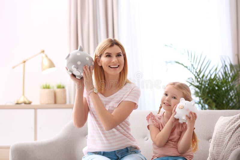 Madre e figlia con i porcellini salvadanaio immagini stock
