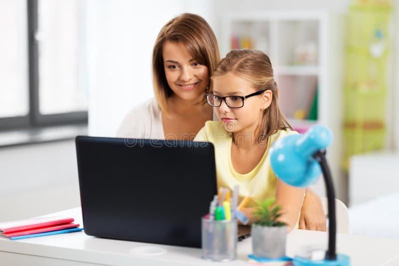 Madre e figlia con il computer portatile che fa compito immagine stock