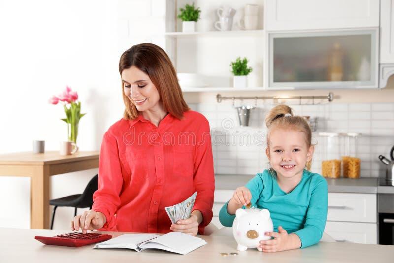 Madre e figlia con soldi alla tavola Soldi di risparmio fotografie stock libere da diritti
