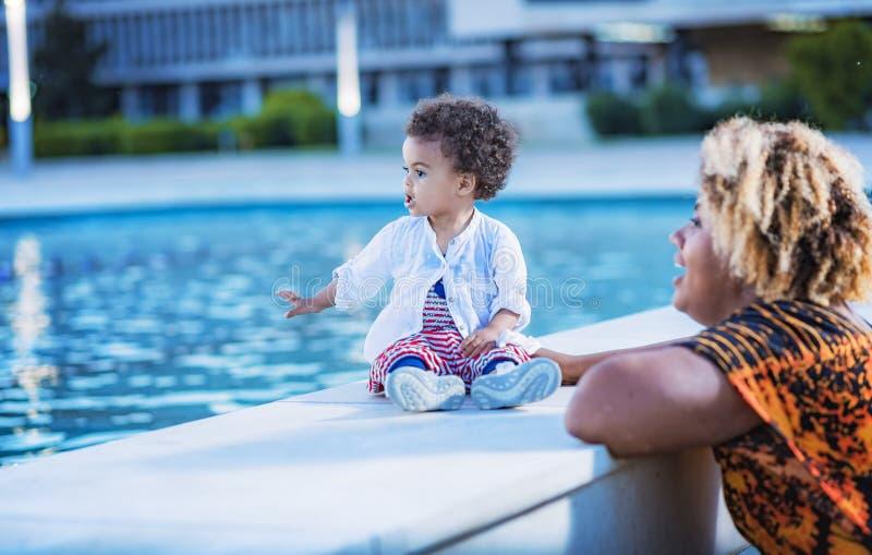 Madre e figlia divertendosi con acqua della fontana fotografie stock