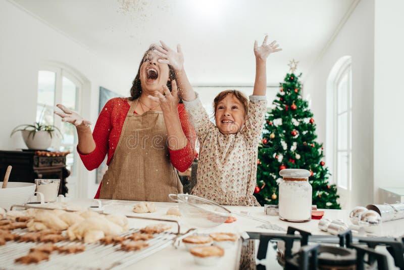 Madre e figlia divertendosi mentre producendo i biscotti di Natale fotografia stock libera da diritti