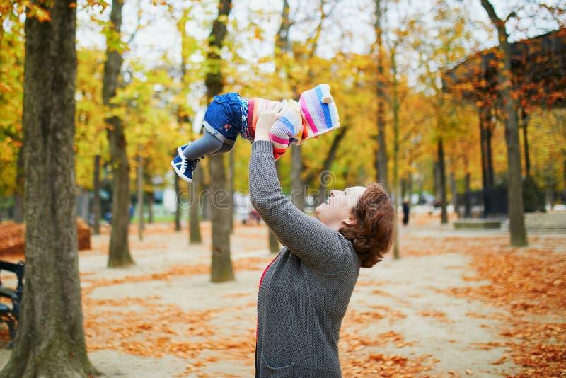 Madre e figlia divertendosi nel parco di caduta fotografia stock