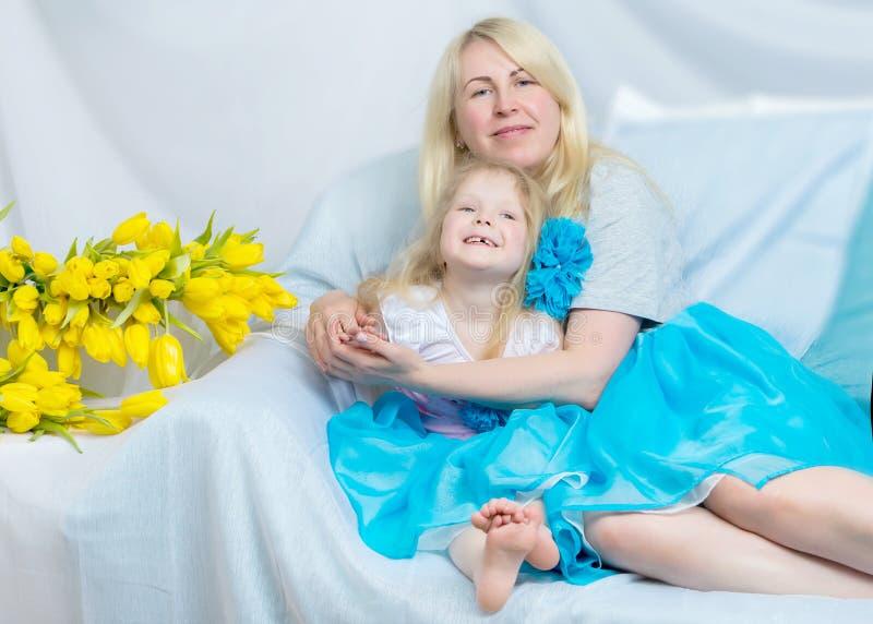 Madre e figlia felici circa i tulipani gialli di sicuro fotografia stock libera da diritti
