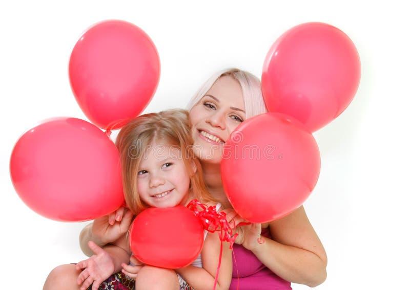 Madre e figlia felici con gli aerostati rossi immagine stock libera da diritti