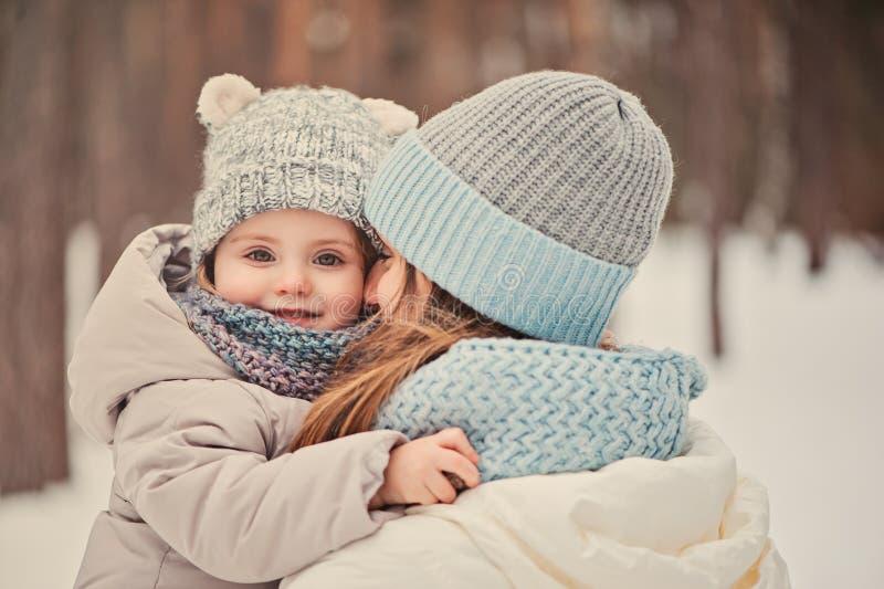 Madre e figlia felici sulla passeggiata nell'inverno nevoso fotografie stock libere da diritti