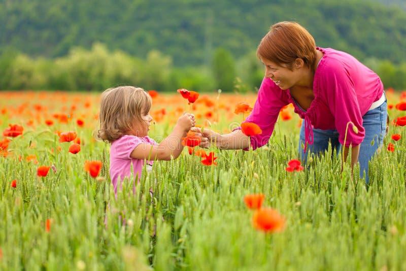 Madre e figlia nel campo del papavero immagini stock libere da diritti