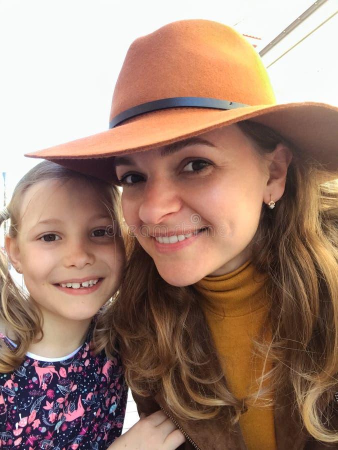 Madre e figlia sorridenti che esaminano macchina fotografica immagini stock