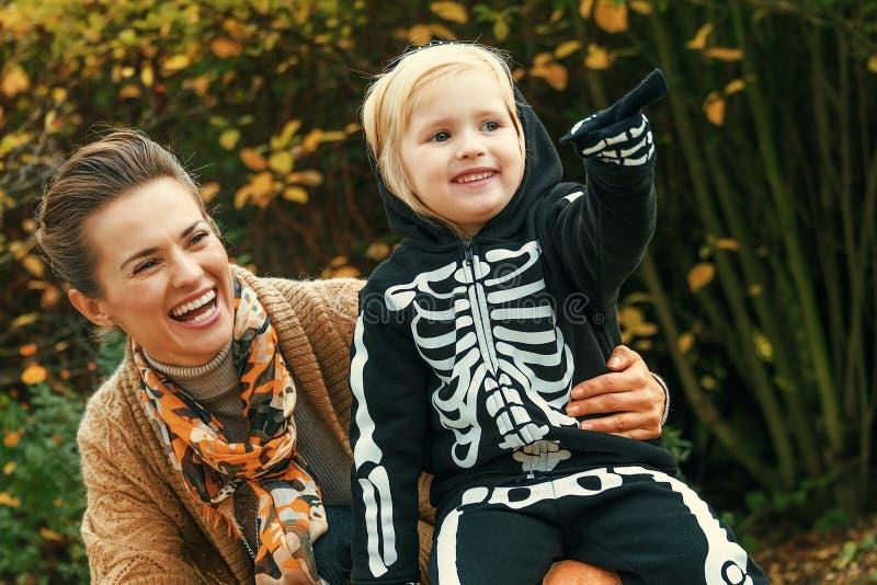 Madre e figlia su Halloween al parco che indicano a qualcosa immagine stock