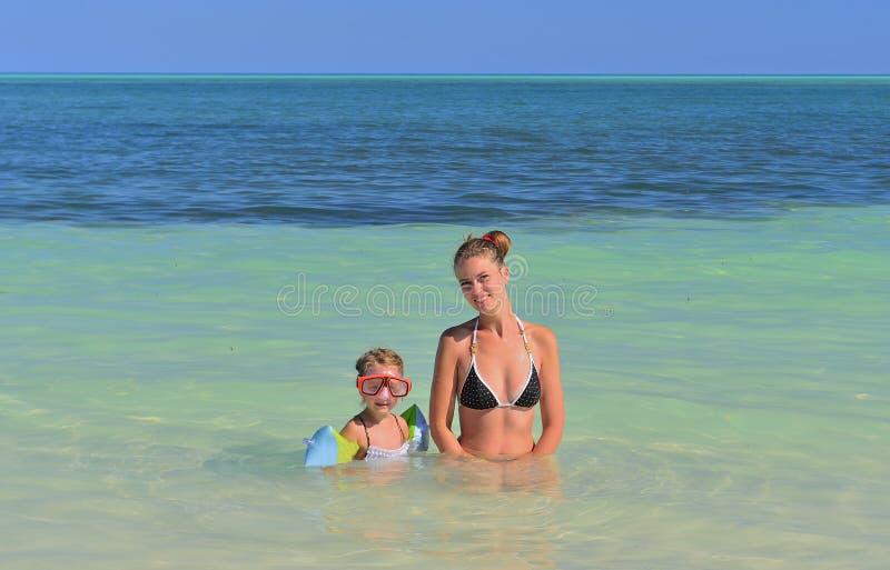 Madre e figlia sveglia che giocano e che nuotano nell'oceano blu fotografie stock