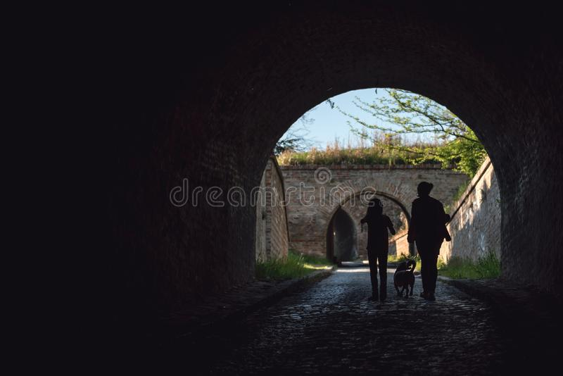 Madre e figlia in un tunnel con un cane fotografia stock