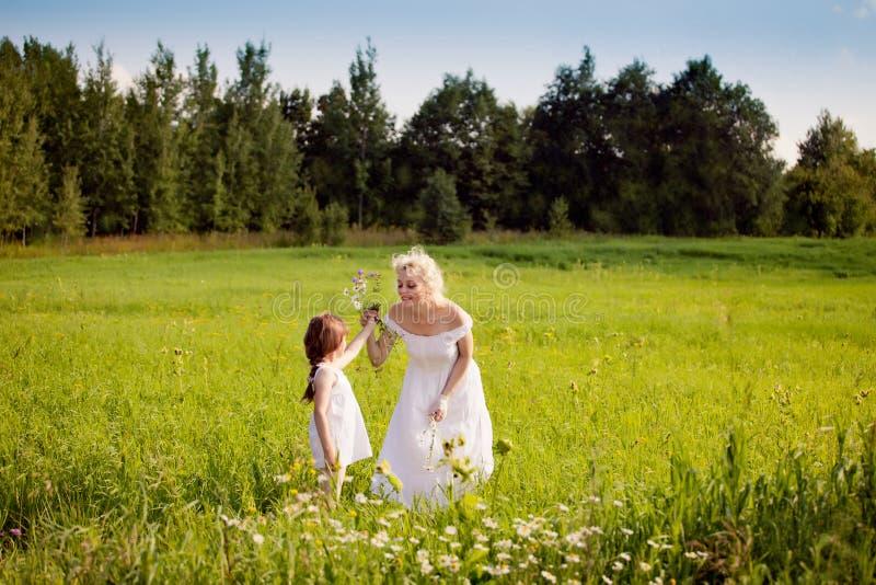 Madre e figlie che si rilassano sul prato fotografie stock libere da diritti