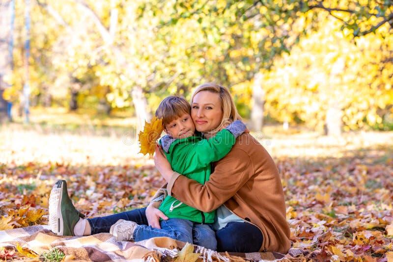 Madre e figlio che abbracciano fra l'autunno all'aperto Concetto di amicizia fra il figlio ed i genitori, famiglia fotografia stock libera da diritti