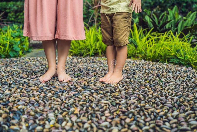 Madre e figlio che camminano su una pavimentazione di ciottolo strutturata, reflessologia Pietre del ciottolo sulla pavimentazion fotografia stock