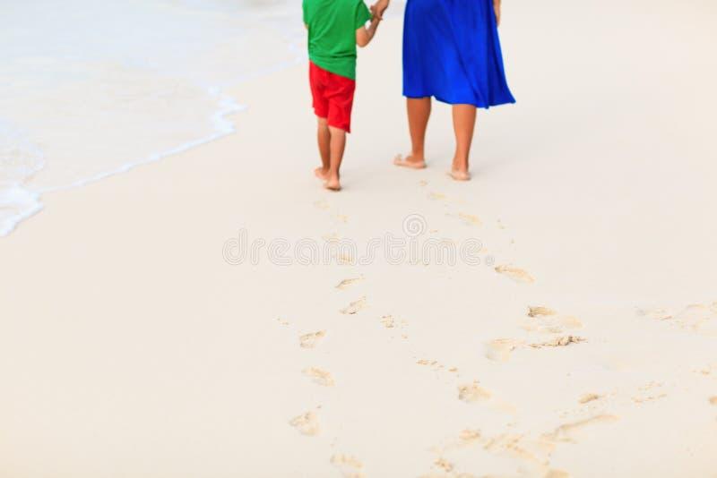 Madre e figlio che camminano sulla spiaggia che lascia orma in sabbia fotografia stock libera da diritti