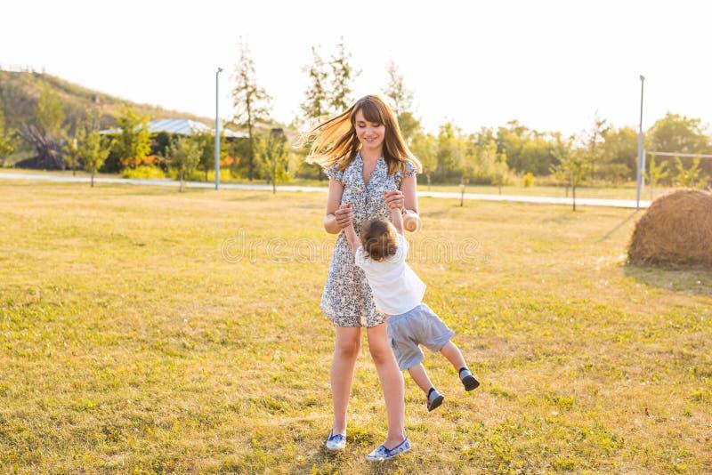 Madre e figlio che filano nel parco di estate fotografie stock libere da diritti