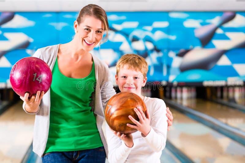 Madre e figlio che giocano al centro di bowling fotografia stock libera da diritti