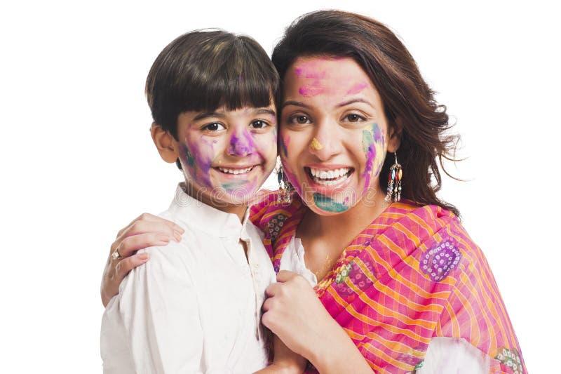 Madre e figlio che godono del holi immagine stock