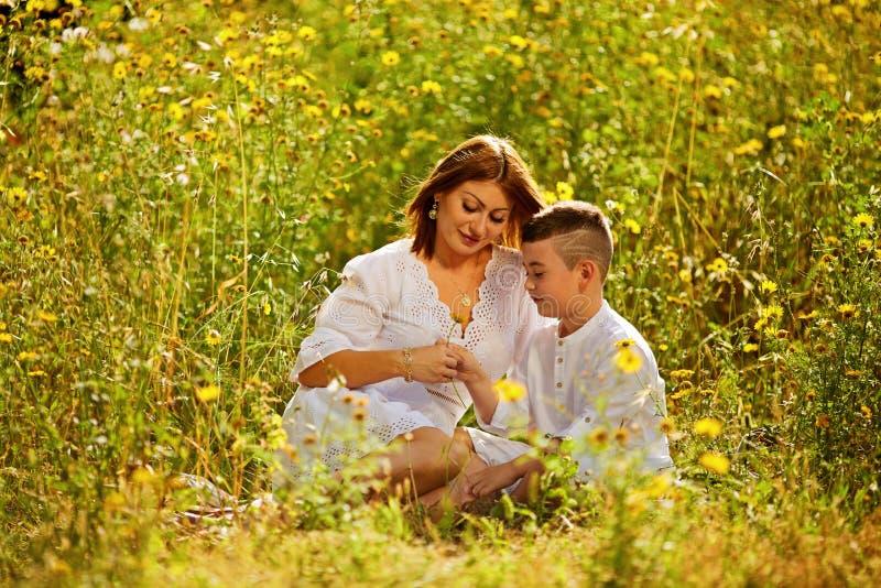 Madre e figlio che hanno divertimento Figlio che la dà a fiori a sua madre Colpo all'aperto immagine stock libera da diritti