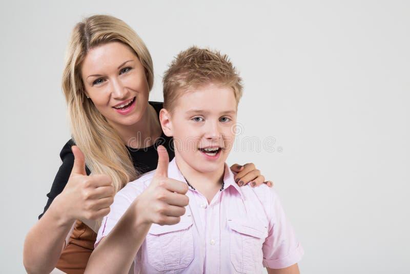 Madre e figlio con capelli biondi che fanno i pollici su immagini stock