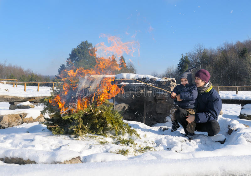 Madre e figlio dal falò nella foresta di inverno fotografia stock libera da diritti