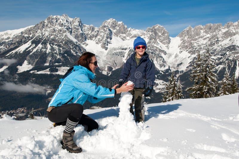 Madre e figlio nella neve di inverno immagine stock libera da diritti
