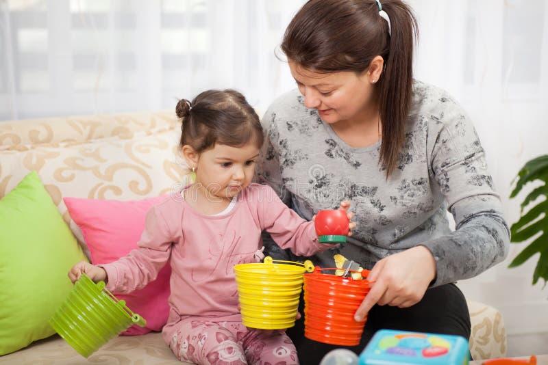 Madre e giovane figlia che giocano con i giocattoli in salone immagini stock libere da diritti