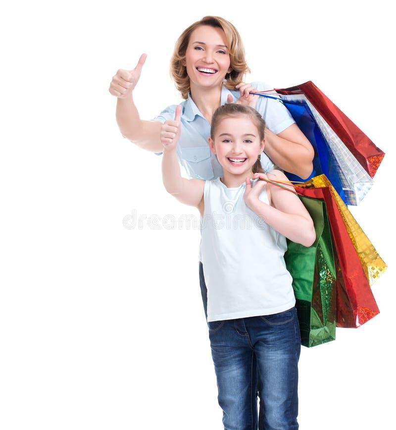 Madre e giovane figlia con i sacchetti della spesa fotografia stock libera da diritti