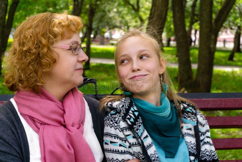 Madre e hija adolescente en un banco de parque fotografía de archivo libre de regalías