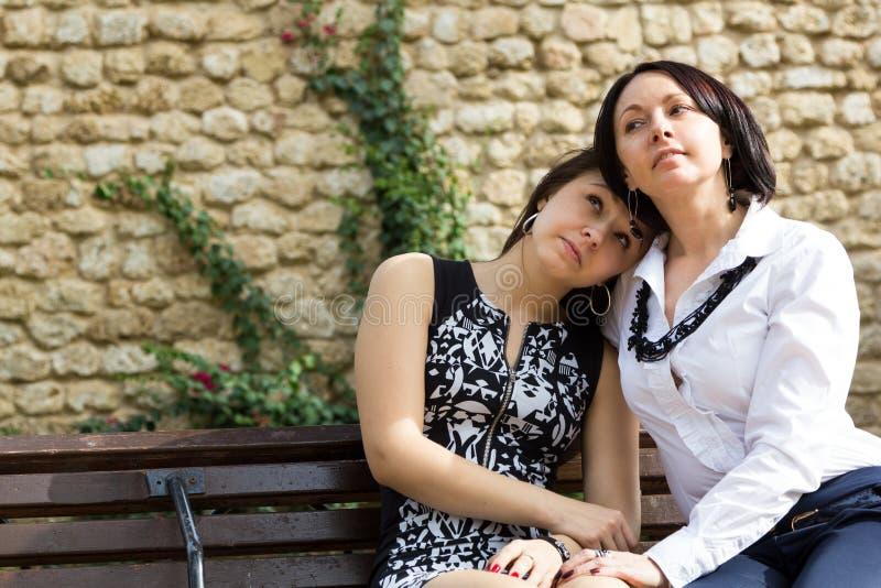 Madre e hija adolescente que se sientan y que sonríen junto imagen de archivo