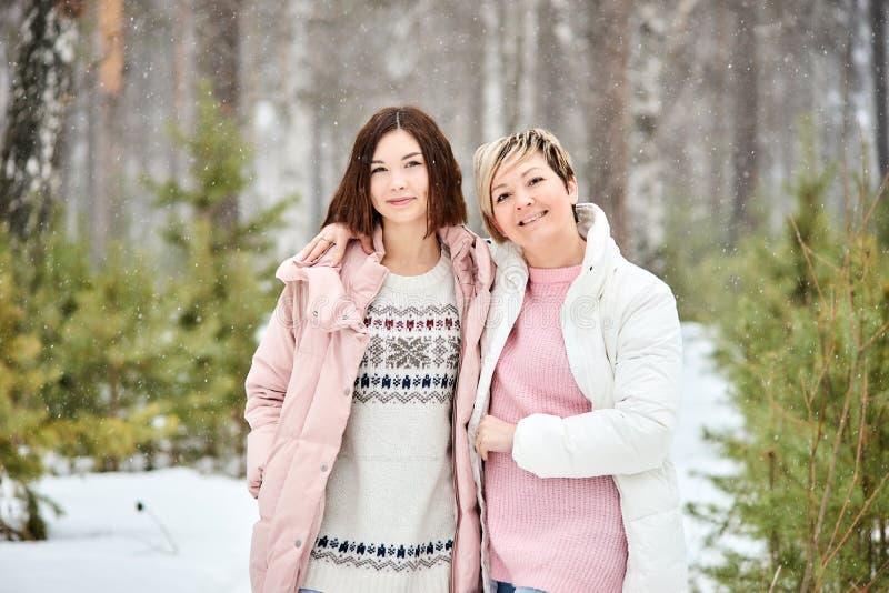 Madre e hija adulta que caminan en nevadas del bosque del invierno fotos de archivo