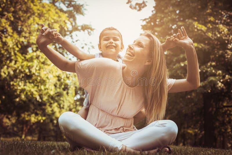 Madre e hija al aire libre en un prado Madre que lleva a su DA imagen de archivo