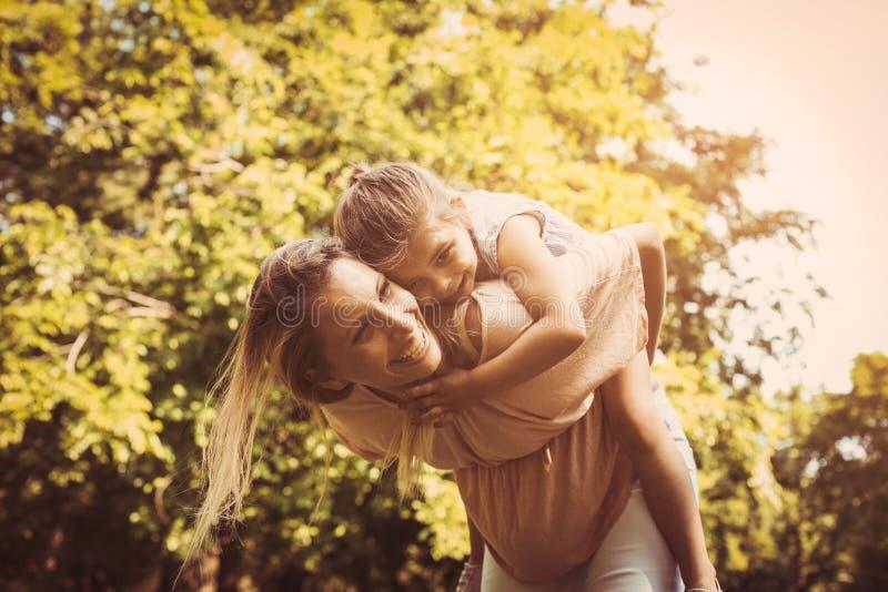 Madre e hija al aire libre en un prado Madre que lleva a su DA imagen de archivo libre de regalías