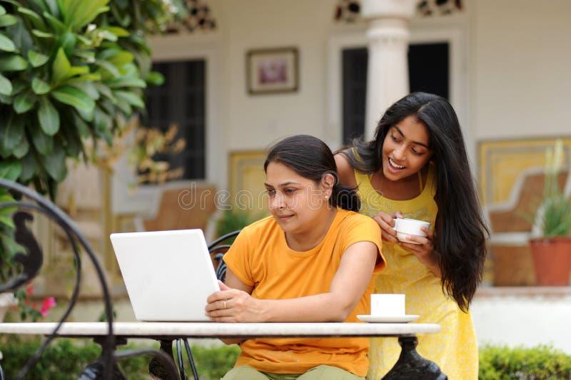Madre e hija cariñosas con la computadora portátil al aire libre fotografía de archivo libre de regalías