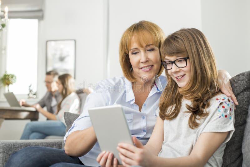 Madre e hija cariñosas que usa la tableta con la familia que se sienta en fondo en casa imagen de archivo libre de regalías