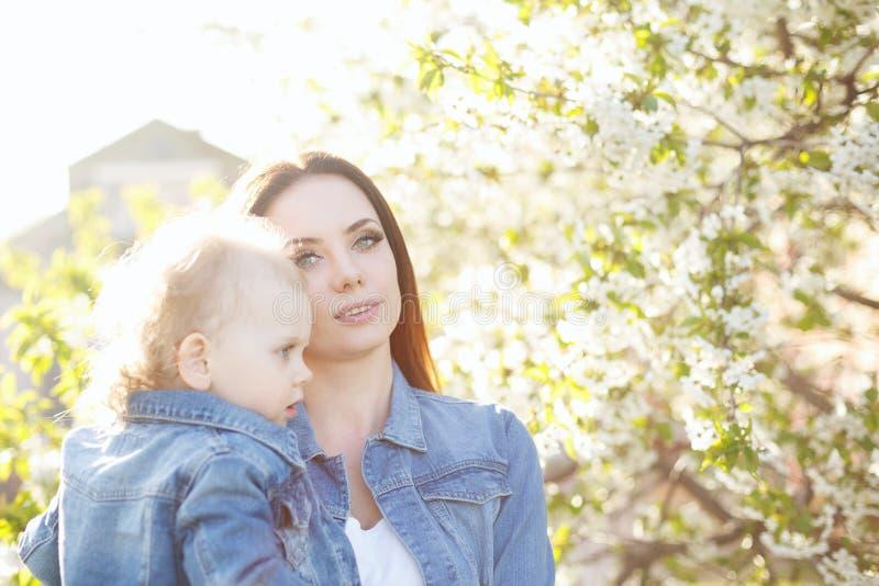 Madre e hija cerca de un árbol floreciente imagen de archivo libre de regalías