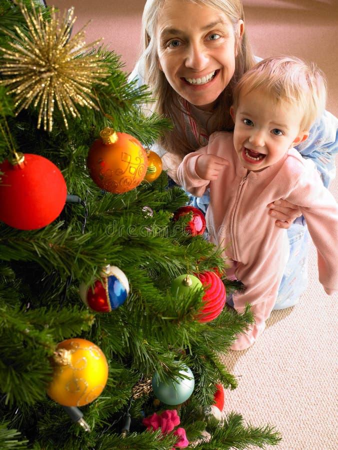 Madre e hija con el árbol de navidad foto de archivo